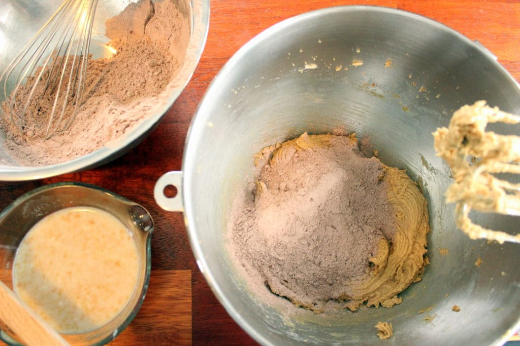 One metal bowl with flour and cocoa powder mixture and metal whisk, one glass measuring cup with milk, vinegar and vanilla mixture and one metal bowl with flour and cocoa powder on top of wet mixture, all on red wood background.