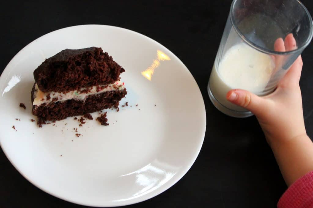 Chocolate cookie Sandwich with icing on white plate with child's hand holding glass of milk on black background.