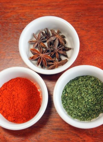 Spices and herbs in small white bowls.