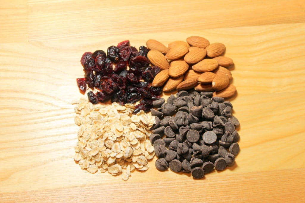 Craisins, almonds, chocolate chips and oats on wood background.