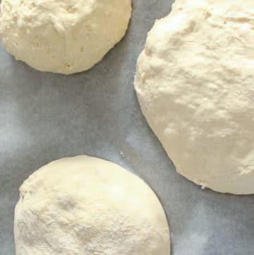 3 balls of pizza dough on parchment paper.