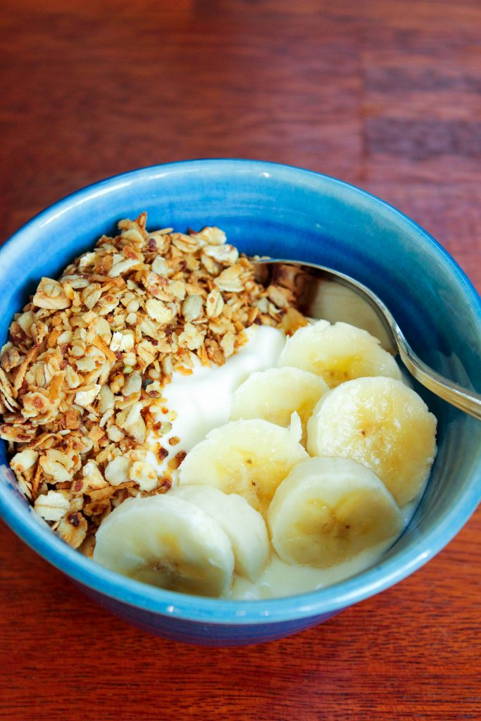Granola, bananas, yogurt and spoon in blue bowl on red wood background.