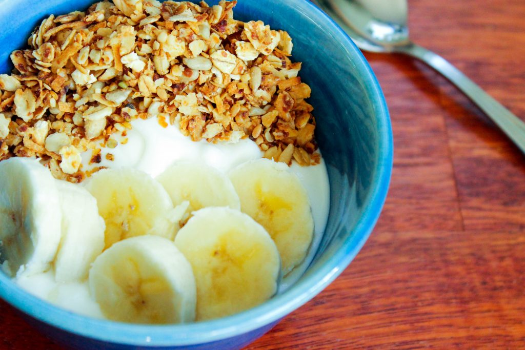 Granola, banana and yogurt in blue dish.