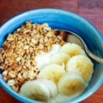 Yogurt, sliced bananas and granola in blue bowl.