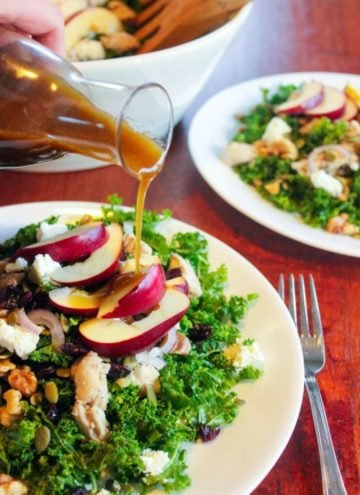 Kale salad topped with vegetables, chicken and apples on white plate.