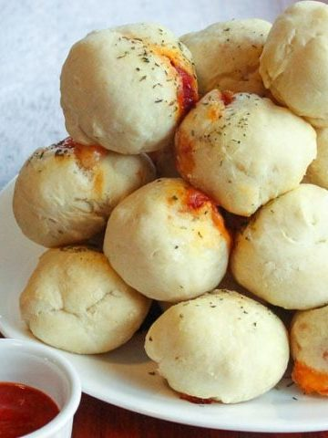 Stack of pizza dough balls on white plate.