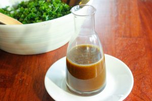 Maple Balsamic Dressing in Glass Jar on White Plate.