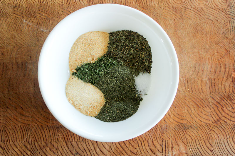Garlic Powder, Onion Powder, Dried Parsley, Dried Basil, Dried Dill, Salt and Pepper inside white bowl on wood background.