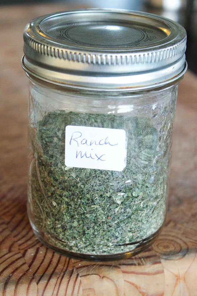 "Glass mason jar with metal cover filled with spice mix, with small label that says ""Ranch Mix"", on wood background."