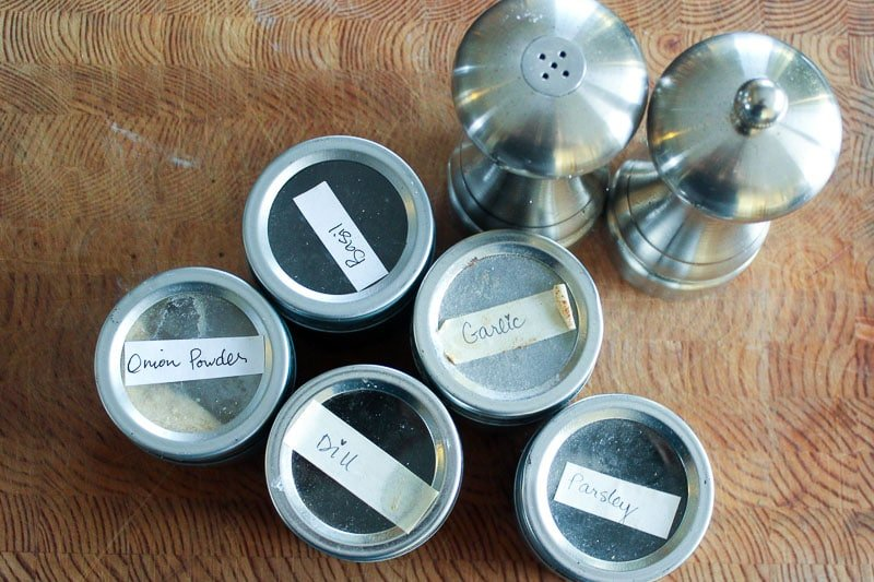 5 metal spice tins and metal salt and pepper shakers on wood background.