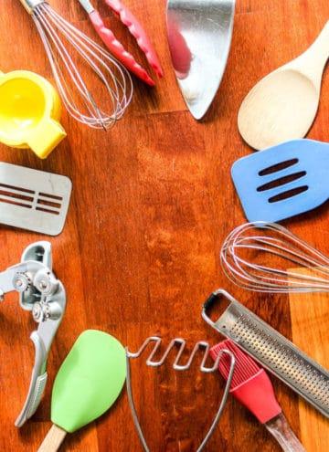 Kitchen utensils on red wood board.