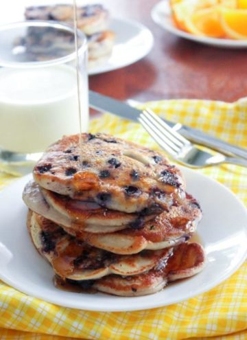 Stack of blueberry pancakes and glass of milk