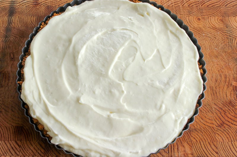 Key lime pie in tart pan on wood background.