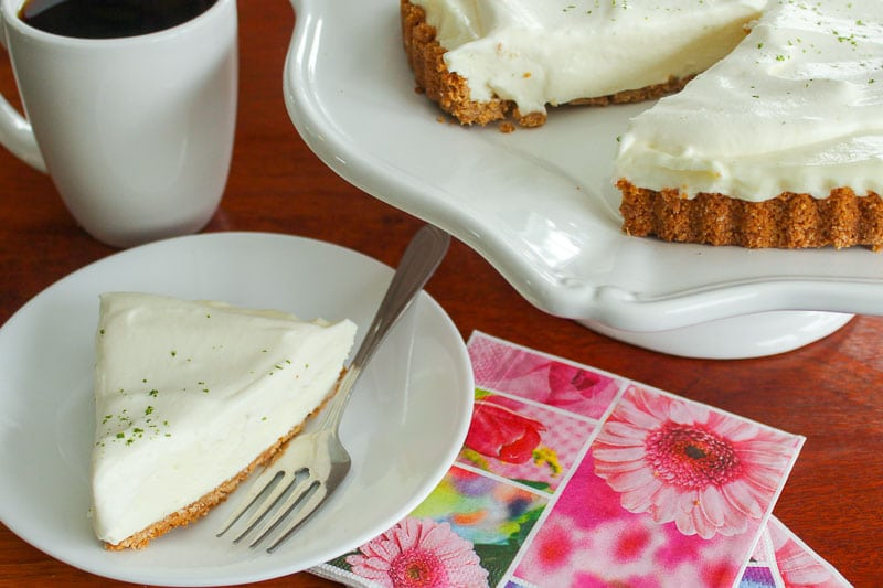 Slice of Key Lime Pie on white plate with cup of coffee and rest of pie in background.