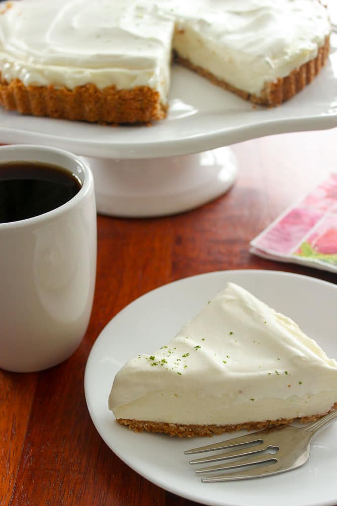 Slice of pie and fork on white plate with coffee and the rest of the pie in background.