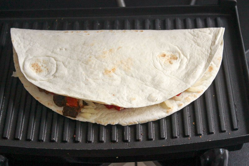 Folded Beef Quesadilla on a panini press.