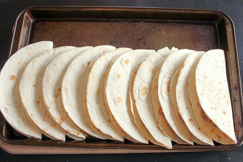 10 folded tortillas on a sheet pan.