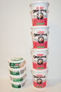 4 stacked tubs of sour cream next to 4 stacked tubs of plain yogurt, on white background.