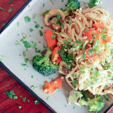 Noodles topped with vegetables and parsley on grey plate.