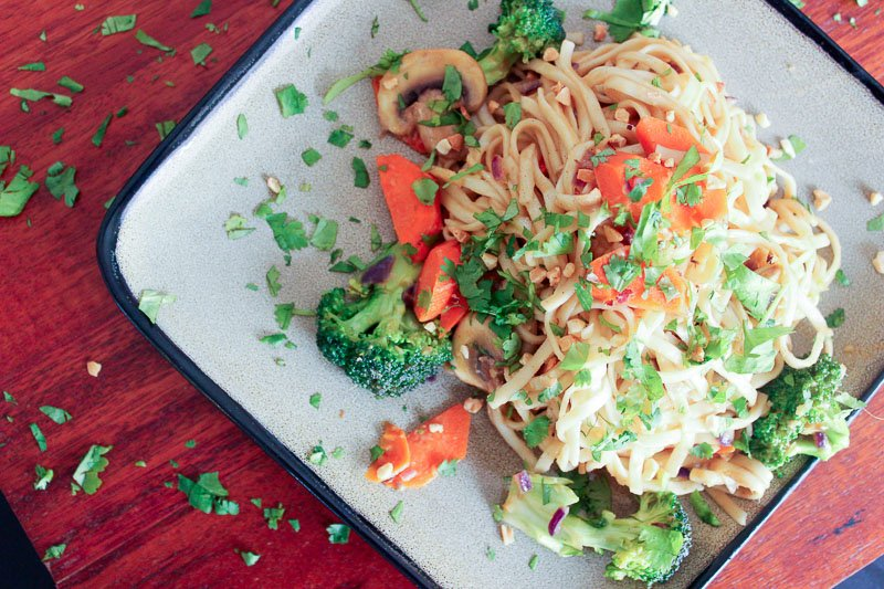Vegetarian Dan Dan Noodles Topped with Parsley on Gray Plate.