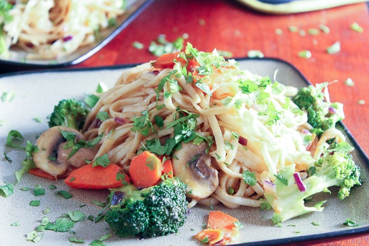 Plate of rice noodles with mushrooms, broccoli, carrots and cilantro