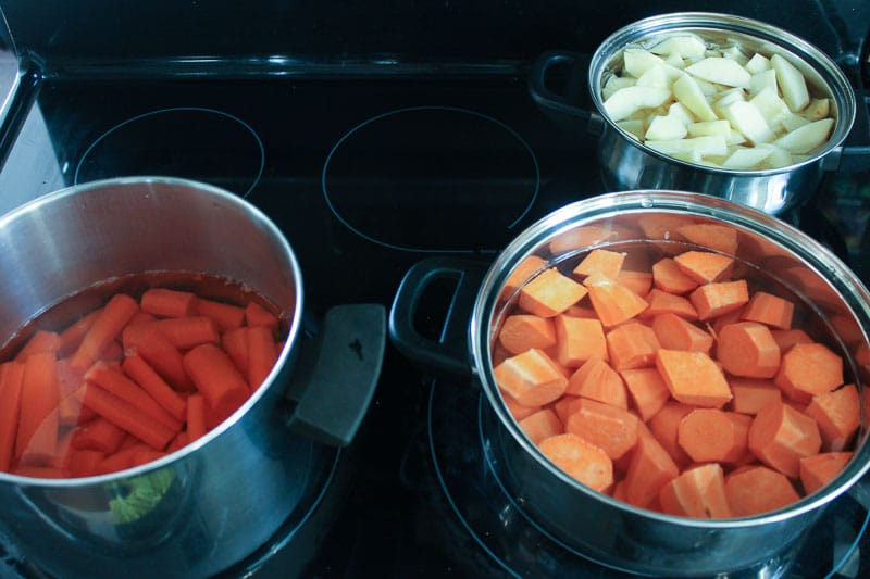 Chopped carrots, sweet potatoes and apples in pots on stove.