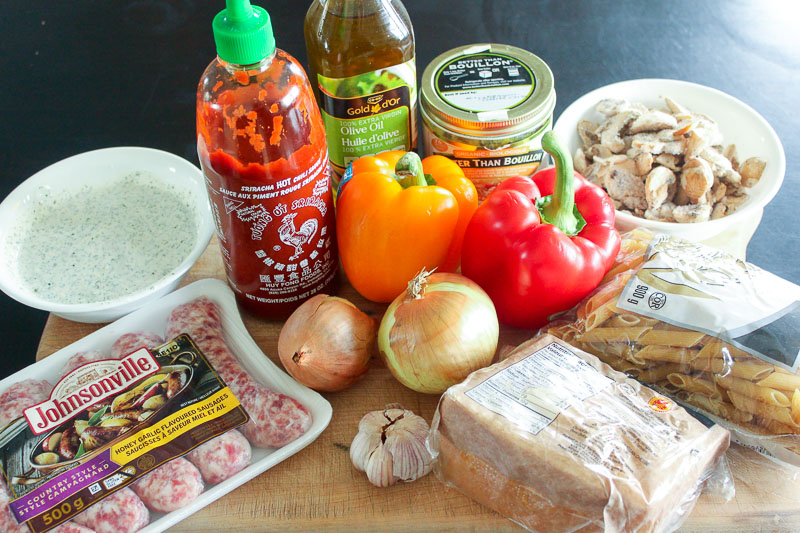 Package of sausages, ranch in white bowl, bottle of Sriracha, bottle of olive oil, can of bouillon, cooked chicken, bag of pasta, block of parmesan cheese, bulb of garlic, 2 white onions, a orange pepper and a red pepper.  All these ingredients on a wood board.