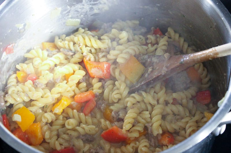 Pasta and vegetables cooking in metal pot.