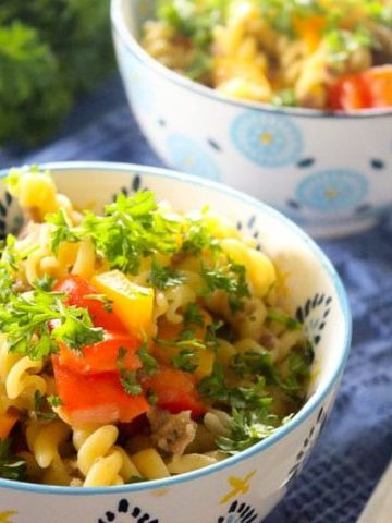 Pasta topped with peppers and parsley in white bowl.
