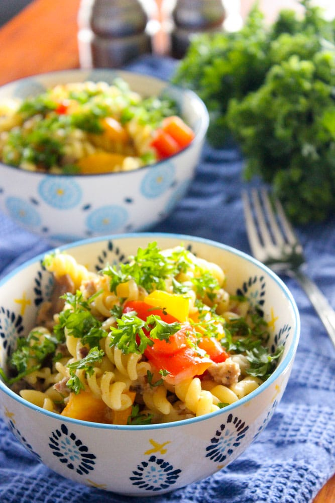 Pasta in white and blue bowls on blue cloth with parsley and fork in background.