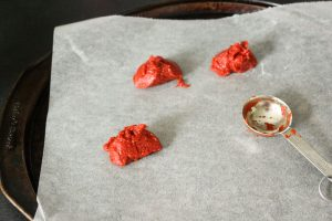 3 mounds of tomato paste and a metal measuring spoon on parchment paper.