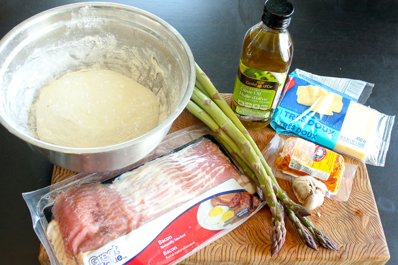 Asparagus Bacon Goat Cheese Pizza Ingredients on Wooden Board.