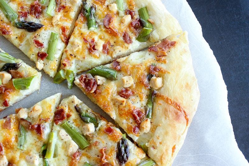 Bacon, asparagus and goat cheese pizza on Parchment Paper.