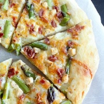 Pizza topped with bacon, asparagus and goat cheese on parchment paper.