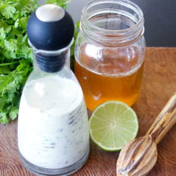 White dressing in glass jar next to honey, lime and cilantro.