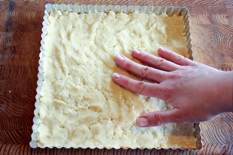 Hand pressing dough in square tart pan.
