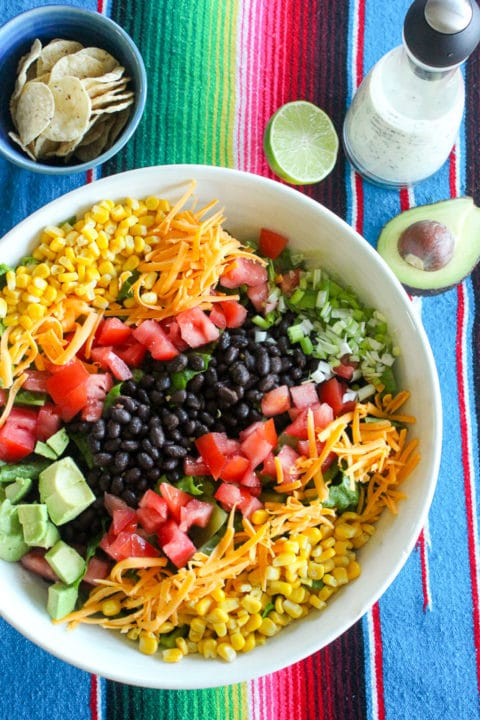 Mexican salad with beans, cheese and vegetables in white bowl.