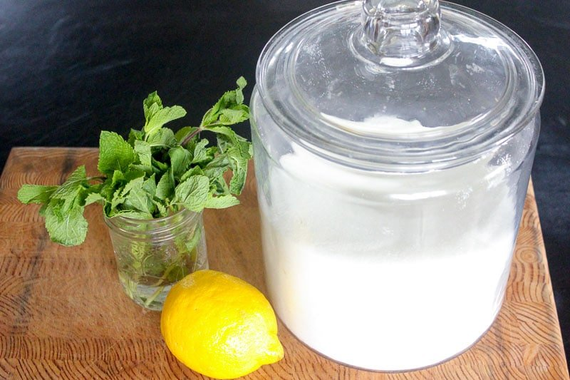 Fresh mint, a lemon and a jar of sugar on Wooden Board.