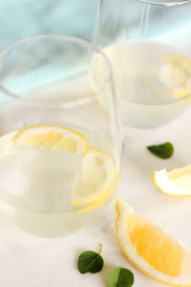Lemons floating in lemonade in 2 glasses with lemon wedges and mint leaves.