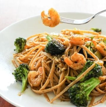 Pasta topped with shrimp and broccoli in white plate.