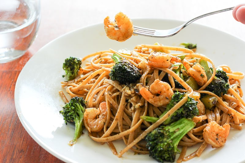 Fork holding shrimp above broccoli and shrimp pasta in white plate with glass of water on red wood background.
