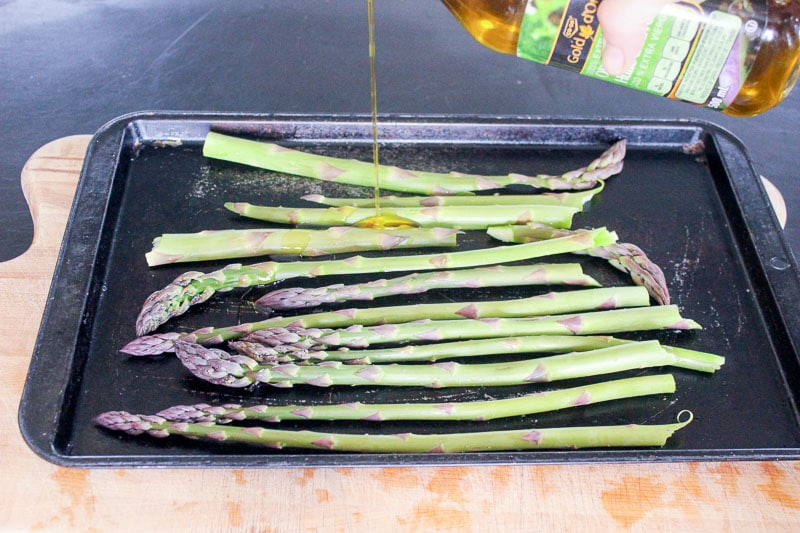 Drizzling olive oil on asparagus stalks on metal sheet pan.