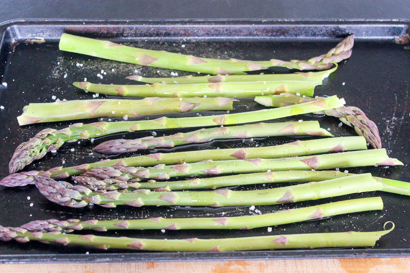Kosher salt on asparagus stalks on metal sheet pan.