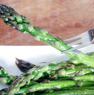 Asparagus stalk on fork and asparagus on white plate.