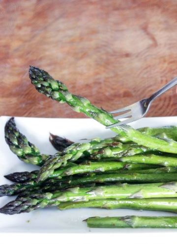 Asparagus stalk on fork and asparagus on white plate.
