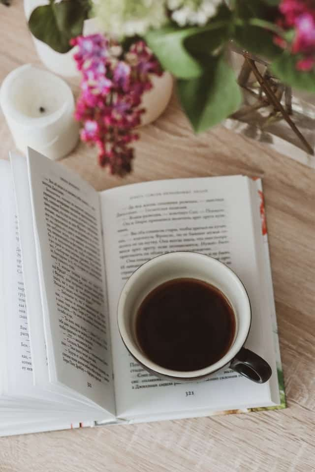 Book with cup of black coffee on it and flowers nearby.