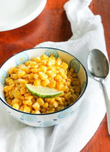 Corn topped with slice of lime in white bowl.