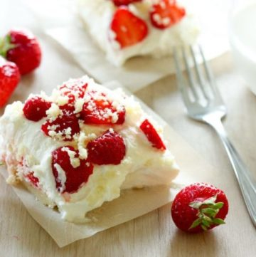 Strawberry shortcake square topped with whipping cream and sliced strawberries.