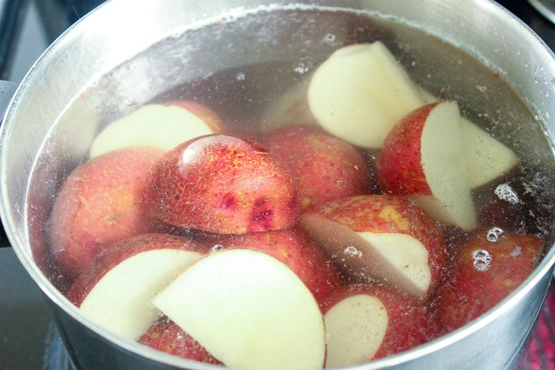 Sliced Red Potatoes in Water in Metal Pot.