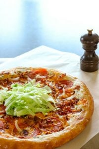 Pizza topped with tomatoes and shredded lettuce on Parchment Paper.